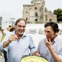 On location: U.S. movie director Oliver Stone (left), and Peter Kuznick, a professor of history at American University, walk near the A-Bomb Dome in Hiroshima on Monday. | AP