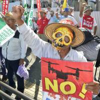Consolidated gripes: A protest is staged Tuesday outside U.S. Marine Corps Air Station Futenma in Ginowan, Okinawa, following the crash Monday of a U.S. Air Force chopper elsewhere in the prefecture and over the additional deployment of MV-22 Osprey aircraft to Futenma. | KYODO