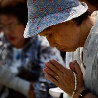 Prayers for peace: Elderly women pray for victims of the 1945 atomic bombing in front of the cenotaph at Peace Memorial Park in Hiroshima on Tuesday as ceremonies are held to mark the 68th anniversary of the bombing. | AFP-JIJI