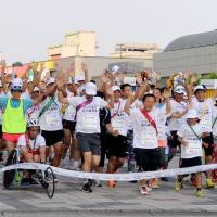 Home stretch: Tokyo Gov. Naoki Inose (without hat) reaches the goal with 101 other runners on Wednesday in Tokyo's Odaiba district. | YOSHIAKI MIURA