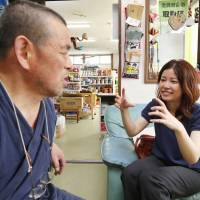 Establishing relations: Makiko Orita, a graduate student at Nagasaki University, visits store owner Yoshiyuki Yanai in Kawauchi, Fukushima Prefecture, for a health consultation July 31. | KYODO