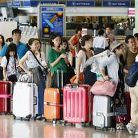 Outward bound: Holidaymakers heading to overseas destinations line up at the check-in counters at Narita airport Saturday as the Bon summer holidays began. | KYODO