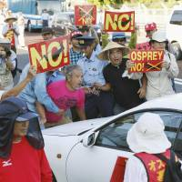 Up in arms: People block a U.S. military car outside Okinawa's Futenma base to protest Monday's Osprey ferry flights. | KYODO