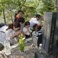 Memorial day: Relatives of victims who died in a Japan Airlines crash on Mount Osutaka, Gunma Prefecture, in 1985 pray Monday in front of a monument to mark the 28th anniversary of the air tragedy. | KYODO