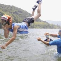 Keeping their cool: A family plays in the Shimanto River on Wednesday in Shimanto, Kochi Prefecture, where the mercury hit a record 41.0 degrees Monday. | KYODO