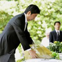 Meaningful gesture: Prime Minister Shinzo Abe lays flowers at the war memorial in Tokyo's Chiyoda Ward on Thursday, the 68th anniversary of Japan's defeat. | KYODO