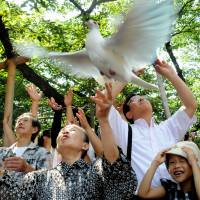High hopes: Symbolizing their wish for world peace, people release doves Thursday at Yasukuni Shrine in Tokyo. | SATOKO KAWASAKI