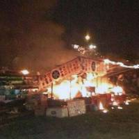 First fatality: A food stall is engulfed by flames after gasoline for a portable power generator ignited Thursday, triggering an explosion at a fireworks festival in Fukuchiyama, Kyoto Prefecture. On Saturday, a woman died from severe burns sustained in Thursday night's blast. | KYODO
