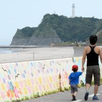Legacy of the lost: Takashi Suzuki, whose daughter, Himeka, 10, was killed by the March 2011 tsunami, walks with his son along the coast of Iwaki, Fukushima Prefecture, on July 10. | KYODO