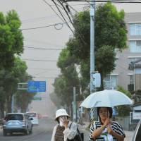 Fallout: People in the city of Kagoshima try to avoid falling ash from Sunday's strong eruption of nearby Mount Sakurajima. | KYODO