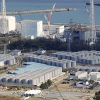 Multitude of problems: Tanks (foreground) containing radioactive water and reactor buildings (background) at the Fukushima No. 1 nuclear plant are photographed in February. | KYODO