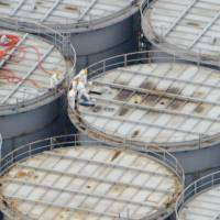 Water woes: Workers stand atop a tank for highly radioactive water at the Fukushima No. 1 nuclear power complex  Tuesday, where one container was found to have leaked 300 tons of water the same day. | KYODO