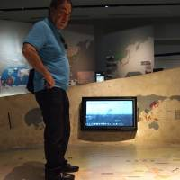The big picture: Oliver Stone checks out a map of Asia at Peace Memorial Museum in Mabuni on Aug. 14. | JON MITCHELL
