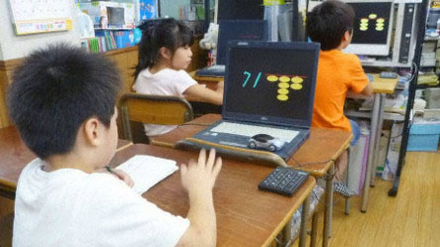 Children practice 'anzan,' or blind calculations, while watching computer screens showing numbers and a scaled-down soroban at a class in Tokyo's Nerima Ward last month.