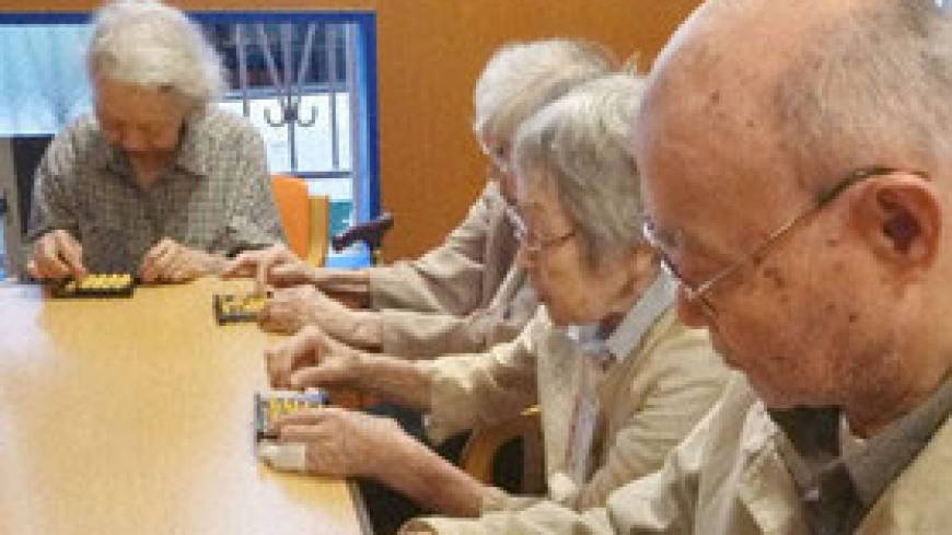 Quick thinking: Senior citizens attend a 'soroban' abacus lesson in Tokyo's Minato Ward in June.