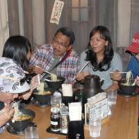 On a high: An Indonesian family eats ramen at the Shinyokohama Raumen Museum, an amusement facility featuring the popular noodles, in Yokohama on Aug. 14. Foreign visitors to Japan in July topped 1 million for the first time, a record high. | KYODO