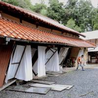 Holding on: A house tilts after being hit by a mudslide Saturday in Hamada, Shimane Prefecture, where more than 36,000 residents were advised to evacuate due to torrential rain. | KYOTO