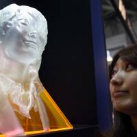 Spitting image?: A woman looks at a rapidly manufactured plastic model of her face that was rendered by a 3-D printer at the 3D & Virtual Reality Exhibition in Tokyo in June. | BLOOMBERG