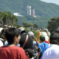 Observers gather to see the launch of the Epsilon rocket carrying the world's first space telescope for observing planets in Kagoshima Tuesday morning before its launch was postponed at the last minutes in the afternoon. | KYODO