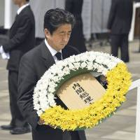 In respect: Prime Minister Shinzo Abe offers flowers for the victims of the Nagasaki atomic bombing Friday at the city's Peace Park to commemorate the 68th anniversary of the attack. | KYODO