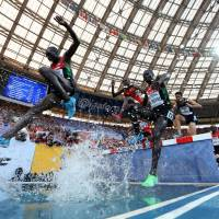 Splashing: Kenyan runners negotiate the water jump during the men's 3,000-meter steeplechase final at the world championships on Thursday in Moscow. Kenya's Ezekiel Kemboi won in a time of 8 minutes, 6.01 seconds. | AFP-JIJI