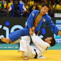 First gold: Naohisa Takato battles Mongolia's Amartuvshin Dashdaava in the 60-kg final at the world championships in Rio de Janeiro on Monday. Takato won the match. | AFP-JIJI