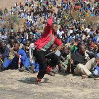 Platinum class: Miners demonstrate at a mountain close to the facility near Rustenburg to demand that their wages be more than tripled. A South African union said a local leader was shot dead at Lonmin's Marikana mine Monday, almost a year after police shot to death 34 strikers in the restive platinum belt. | AFP-JIJI