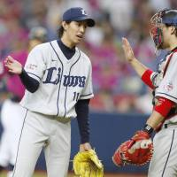 Takayuki Kishi (left) trades high fives with Ginjiro Sumitani during Sunday night's game against the Orix Buffaloes. | KYODO