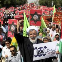 Leading the crowd: An Iranian cleric holds an anti-Israeli placard as he chants slogans while attending an annual pro-Palestinian rally marking Al-Quds (Jerusalem) Day in Tehran on Friday. | AP