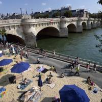 Urban beach: Parisians sunbathe on a bank of the Seine River at the beginning of the annual Paris Plages event. | AFP-JIJI