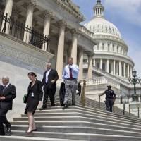 Getting out of Dodge: Lawmakers walk down the steps of the House of Representatives on Capitol Hill on Friday as they prepare to leave town for a five-week recess. | AP