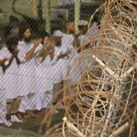 Staying put: Detainees pray before dawn near a razor-wire fence at the U.S. military prison in Guantanamo Bay, Cuba, in 2009. | AP