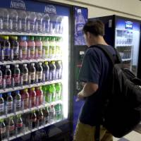 Sugar is sugar: A student in Connecticut buys a soft drink in the school cafeteria. While few parents believe sodas are good for their kids, many of them don't realize that 'healthy' fruit drinks can contain nearly as much sugar as a can of cola. | BLOOMBERG