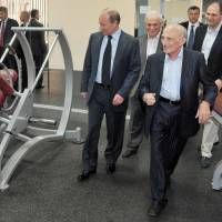 Longtime friends: Russian President Vladimir Putin walks with Anatoly Rakhlin (right), his childhood mentor and judo teacher, while visiting a sports school in St. Petersburg on May 30. | AP