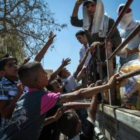 Winning young minds: Members of an Islamist rebel group distribute toys and other treats to children at a public park in the Islamic State of Iraq and the Levant stronghold of Raqqah on  Thursday. | AFP-JIJI