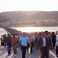 Iraqi haven: Syrians stream across a bridge over the Tigris River into the autonomous Kurdish region of northern Iraq on Thursday. | AFP-JIJI