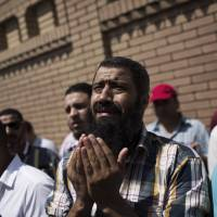 In mourning: A friend of Ammar Badie, the son of Mohammed Badie, the Muslim Brotherhood's spiritual leader, cries during his funeral Sunday. Badie was killed Friday by security forces during violent clashes in Cairo. | AP