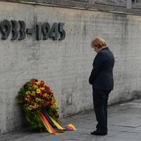 Site of infamy: German Chancellor Angela Merkel attends a wreath-laying ceremony at Dachau on Tuesday during her visit to the concentration camp where more than 41,000 persons were killed, starved or died of disease during the Nazis' reign from 1933 to 1945. | AP
