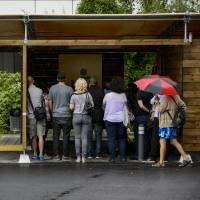 Sex and the city: Visitors inspect boxes at a Zurich sex drive-in during an 'open doors event' on Saturday. | AFP-JIJI