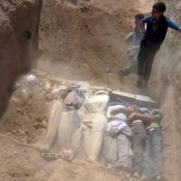 Massacre: This image from a video uploaded on YouTube by the Local Committee of Arbeen allegedly shows Syrians burying victims of a toxic gas attack by pro-government forces in eastern Ghouta and Zamalka, on the outskirts of Damascus. | AFP-JIJI