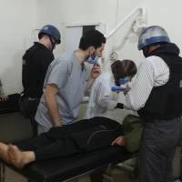 Probing the claims: U.N. chemical weapons experts visit victims of an alleged gas attack at a hospital in Damascus on Monday. | REUTERS/KYODO