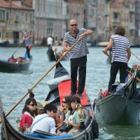 Oar not: Tourists ride gondolas on a canal in Venice on Thursday. | AFP-JIJI