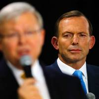 All ears: Australian opposition leader Tony Abbott (right) listens to Prime Minister Kevin Rudd in Brisbane on Aug. 21. | AFP-JIJI