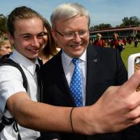 Battle for leader: Australian Prime Minister Kevin Rudd poses with a student from St. Edward's College in Gosford in New South Wales on Friday. | AFP-JIJI,