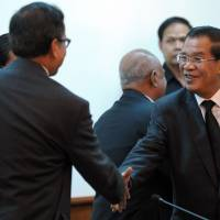 Cooler heads: Cambodian Prime Minister Hun Sen (right) shakes hands with Sam Rainsy, leader of the opposition Cambodia National Rescue Party, during a meeting at the National Assembly in Phnom Penh on Monday. | AFP-JIJI