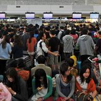 Trying to flee: Passengers crowd around airline counters at Hong Kong's Chek Lap Kok Airport as Typhoon Usagi approaches on Sunday. | AFP-JIJI