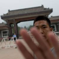 Follow the rules: A plainclothes police officer attempts to stop photographs from being taken outside Qincheng Prison, on the outskirts of Beijing, earlier this month. The prison is where fallen highflier Bo Xilai is expected to be incarcerated. | AFP-JIJI