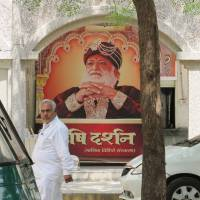 Guilty guru?: An image of Asaram Bapu, arrested last month on charges of sexually assaulting a 16-year-old girl, adorns the walls of his ashram in Motera, India, on Sept. 8. | THE WASHINGTON POST