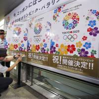 Welcome to the world: Subway station attendants in Tokyo put up posters that commemorate the decision to award the 2020 Olympics and Paralympics to the capital last week. | AP