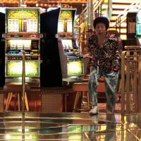 Gambling gal: A woman leaves a casino aboard the Royal Caribbean Cruises Ltd.'s Voyager of the Seas, berthed at Tokyo's Ohi wharf on Sept. 14. Some believe casinos in Japan will become a possibility when the Diet resumes next month. | BLOOMBERG